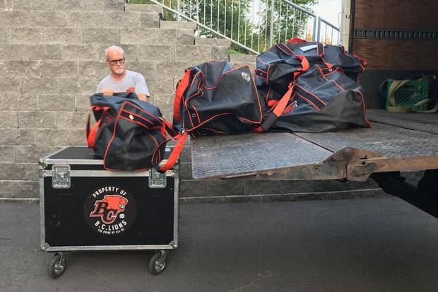 An equipment manager for the B.C. Lions unloads gear from a truck.