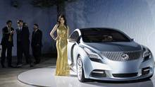 A model stands next to a Buick Riviera at the Auto China 2008 auto show in Beijing in 2008. (Oded Balilty/AP Photo)
