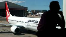 In a file picture taken on Oct. 31, 2011, a passenger waits for Qantas flights to resume service at Sydney International airport. (MARIANNA MASSEY/MARIANNA MASSEY/AFP/Getty Images)