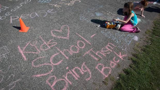 Kids and parents opposed to the teachers' strike write in chalk on the False Creek seawall near Charleson Park in Vancouver. (DARRYL DYCK/THE GLOBE AND MAIL)