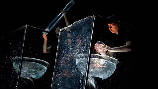 "Act I, Water: Percussionists Yuri Yamashita, Chihiro Shibayama and Haruka Fujii stand at three stations suspended above the stage, each equipped with a large bowl of tap water, which they proceed to slap, drip and, as the score instructs, ""collect the water in two hands"" and ""violently throw collected water into water basin."" The bowls are miked, so a small bouncy ball rubbing up against a Beijing Opera gong creates an ominous wail, while water draining out of a strainer becomes a trickling waterfall, underscoring the lush orchestra music. Fujii has been with the show since its workshop in Shanghai and world premiere in Tokyo in 2002; the others joined in Santa Fe, for the North American premiere in 2007. The years of experience are valuable; unlike the musicians in the orchestra, they work without having the score in front of them. (Rafal Gerszak for The Globe and Mail)"