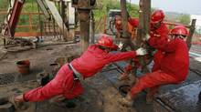 Labourers work at a well head in a PetroChina oil field in Tongnan, southwest China's Sichuan province. (STRINGER SHANGHAI/REUTERS)