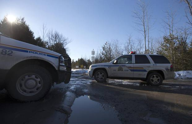 RCMP vehicles are seen down Roxham Road near the Canada-U.S. border in Hemmingford, Que.