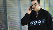Toronto Blue Jays general manager Alex Anthopoulos talks on his cell phone during baseball spring training in Dunedin, FL, on Wednesday, Feb. 16, 2011. (Nathan Denette/THE CANADIAN PRESS)