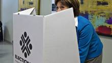 B.C. Liberal Leader Christy Clark jokingly peeks while voting in the provincial election on the first day of advance polling in Burnaby, B.C. on May 8, 2013. (Andy Clark/Reuters)