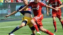 TFC's Justin Braun (right) fights for the ball against New York Red Bulls' Markus Holgersson (left) during the fist half of their MLS game Saturday July 20, 2013 in Toronto. (Jon Blacker/THE CANADIAN PRESS)