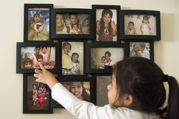 Mackaylah points to a wall of framed pictures of her siblings and parents.