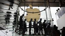 In this Sept. 24, 2011, file photo, customers walk past a huge Apple logo at the new store which is located on two floors linked by a glass spiral staircase in Hong Kong's upscale International Financial Center Mall. Friday, January 24, 2014, marks thirty years after the first Mac computer was introduced, sparking a revolution in computing and in publishing as people began creating fancy newsletters, brochures and other publications from their desktops. (AP Photo/Kin Cheung) (Kin Cheung/AP)
