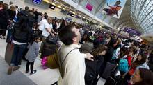 Long waits can drive travellers mad, but airports can cash in on concession sales. (Peter Power/The Globe and Mail)