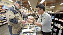 Kit Poon, owner of Main Street Home Health Pharmacy in Stony Plain, helps customer Randy Ulmer with a blood glucose monitoring device. (Jason Franson/The Globe and Mail/Jason Franson/The Globe and Mail)