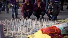An Indian family lights candles in memory of a gang-rape victim in New Delhi, India, Saturday, Jan. 5, 2013. Passers-by refused to stop to help a naked, bleeding gang-rape victim after she was dumped from a bus onto a New Delhi street, and police delayed taking her to a hospital for 30 minutes, the woman's male companion said in an interview. (Altaf Qadri/AP)