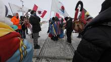 Four aboriginal protestors prepare to be arrested at a blockade of a CN railroad track just west of Portage La Prairie, Man., on Wednesday, January 16. (JOHN WOODS/THE CANADIAN PRESS)