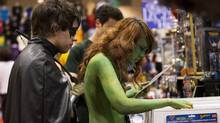 People dressed as the comic book characters Robin and Poison Ivy explore at the Fan Expo convention. (MICHELLE SIU/THE CANADIAN PRESS)