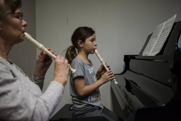 Instructor Ruth Schmid plays recorder with nine-year-old Margarita Tarnapolski, right, on the recorder at the Dixon Hall Music School in Toronto on Dec. 19, 2017.