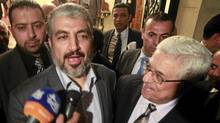 Hamas leader Khaled Meshaal, left, and Palestinian President Mahmoud Abbas speak to the media after their meeting in Cairo, Feb. 22, 2012. (ASMAA WAGUIH/REUTERS/ASMAA WAGUIH/REUTERS)