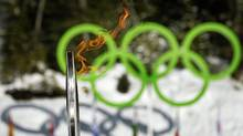 The Olympic torch is seen next to the Olympic rings as it arrives at the biathlon track in Whistler, B.C., on Friday, Feb. 5, 2010. (Anja Niedringhaus)