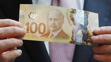 Mark Carney, governor of the Bank of Canada and chairman of the Financial Stability Board, holds the new Canadian 100 dollar bill made of polymer in Toronto, Nov. 14, 2011. (MARK BLINCH/REUTERS)