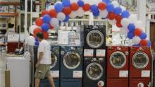 File photo of a shopper passing a display of washing machines at a store in Chicago. (M. Spencer Green/AP)