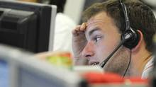 PAUL HACKETT Caption: A trader checks screen data at the IG Index trading floor in London (Paul Hackett/Reuters)
