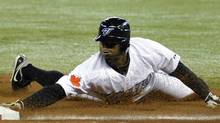 Toronto Blue Jays base runner Rajai Davis slides back into first base ahead of the tag by Minnesota Twins pitcher Carl Pavano (L) during a run down between first and second base in the first inning of their MLB American League baseball game in Toronto April 1, 2011. REUTERS/Mike Cassese (MIKE CASSESE)