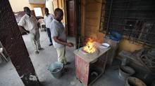 Kweku Boohene, a goldsmith in Accra, Ghana, works by the smelter in the cluttered workshop of Said's Jewellery. (Iain Marlow/The Globe and Mail)