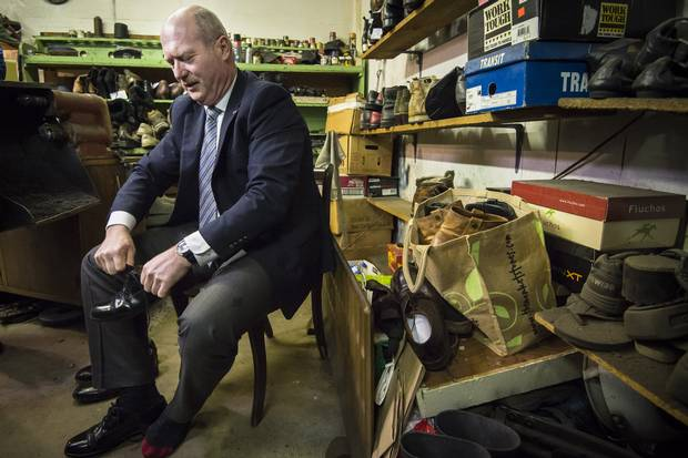 B.C. Finance Minister Mike de Jong tries on his resoled shoes from the Olde Towne Shoe Repair in Victoria on the day before the budget.