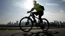 A man is silhouetted by the sun as he rides his bicycle along the seawall in Stanley Park in downtown Vancouver. (JONATHAN HAYWARD/THE CANADIAN PRESS)
