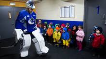 Vancouver Canucks' goalie Roberto Luongo walks past a group of children from a daycare who came to watch the team's informal hockey practice at the University of British Columbia in Vancouver, B.C., on Friday January 11, 2013. (The Canadian Press)