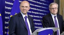 French Finance Minister Pierre Moscovici, left, and Olli Rehn, the European Union's economics commissioner, say the euro zone's bailout fund should be allowed to help ailing banks. (Sebastien Pirlet/Reuters)