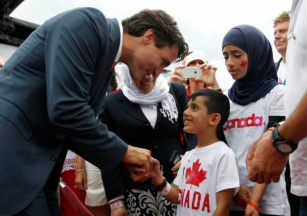 Prime Minister Justin Trudeau shakes hands with a Syrian refugee during Canada Day celebrations on Parliament Hill in 2016.