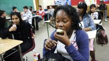 TORONTO: MAY 11, 2012-- Grade 11 student Divine Kibinda eats an apple that was provided to her class as part of a breakfast program at Emery Collegiate Institute in Toronto on Friday, May 11, 2012. School nutrition programs are set to receive more funding from Ontario. (Michelle Siu For The Globe and Mail)