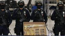 "Mexican federal police officers stand guard behind an AK-47 rifle and ammunition, confiscated during the arrest of suspect Ramiro Pozos Gonzalez, alias ""El Molca"", a suspected leader and founder of the criminal organization known as The Resistance, during a presentation to the media at the federal police headquarters in Mexico City on Sept. 12, 2012. (Bernardo Montoya/REUTERS)"