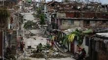 People walk on a street littered with debris after Hurricane Sandy hit Santiago de Cuba Oct. 26, 2012. (DESMOND BOYLAN/REUTERS)