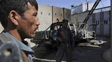 Afghan policemen keep watch near the wreckage of a burned-out vehicle at the UN headquarters in Mazar-i-Sharif on April 2, 2011, after protesters attacked the compound April 1. (SHAH MARAI/AFP/Getty Images)