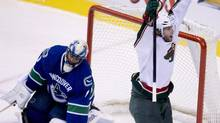 Vancouver Canucks goalie Roberto Luongo (1) looks on as Minnesota Wild center Matt Cullen (7) celebrates his goal during third period NHL action at Rogers Arena in Vancouver, B.C. Monday, March,18, 2013. (JONATHAN HAYWARD/THE CANADIAN PRESS)