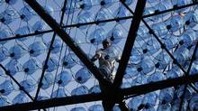 BLUE-SKYING: A worker builds a sculpture made of 7000 recycled plastic water bottles fitted with LED lights at Victoria Park in Hong Kong. (BOBBY YIP/REUTERS)