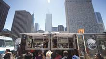 People wait in line to get food from 'Food Dudes' in Toronto's Nathan Phillips Square during the launch of Toronto's Food Truck Pilot Program July 25, 2013. (Gloria Nieto/The Globe and Mail)