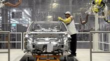 Volkswagen autoworker Greg Wood works in the chisel checks department in the company in this Dec. 1, 2011, file photo. (Billy Weeks/Reuters)
