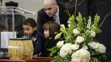 Toronto, Ontario - January 3, 2014 -- Christopher Peloso -- Former Ontario cabinet minister George Smitherman looks at the urn for his late husband Christopher Peloso along with their two children, Michael, 5, and Kayla, 3 during a memorial service in Toronto, Friday January 3, 2014 (Mark Blinch for the Globe and Mail) Christopher Peloso, 40, was found dead by police earlier this week after he went missing. (Mark Blinch For The Globe and Mail)