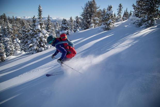 Tessa Treadway skis with her son Raffi on her back near Tweedsmuir Ski Club.