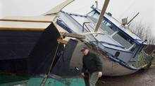 Chuck Hunziker inspects the stern of his friend Tam Flemming's 45-foot schooner in Barrachois, N.S. on Wednesday, Dec. 22, 2010. Both the schooner and the fishing boat floated off their cradles after a storm surge hit the marina. The third Atlantic storm in a month crashed through seawalls, flooded wharfs and damaged homes along the east coast. (Andrew Vaughan/The Canadian Press/Andrew Vaughan/The Canadian Press)
