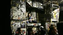 A pair of patrons (C) sit on top of a sticker covered speaker inside the music venue CBGB in New York City October 14, 2006. CBGB is closing on October 15 after 33 years as a music venue. (LUCAS JACKSON/REUTERS)