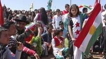 A Syrian girl wearing a dress depicting the Syrian opposition flag holds a Kurdish flag during a rally protesting against Syriaian President Bashar al-Assad in the Kurdish community in Hasaka, Syria, in this picture provided by Shaam News Network on March 21, 2013. (REUTERS)