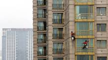 Workers clean the windows of an apartment block at a residential area in Beijing May 9 2012. (PETAR KUJUNDZIC/PETAR KUJUNDZIC/REUTERS)