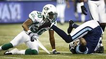 Toronto Argonauts Maurice Mann is tackled by Saskatchewan Roughriders' Terrell Maze (L) during the first half of their CFL football in Toronto, October 8, 2012. (Mark Blinch/REUTERS)