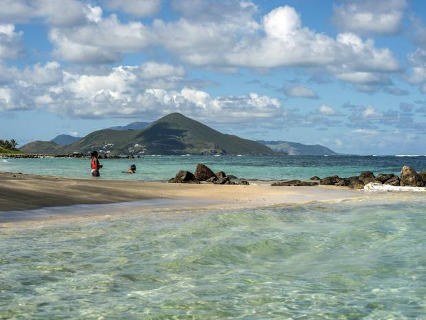 People swim in the Caribbean Sea in Long Haul Bay, Nevis. Newcastle Bay and the island of St. Kitts are in the background.