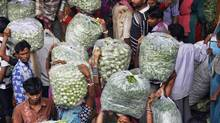 People carry vegetable bags at a wholesale vegetable market in the western Indian city of Ahmedabad on Aug. 14, 2012. India's wholesale inflation rate unexpectedly fell in July to 6.87 per cent. (AMIT DAVE/REUTERS)