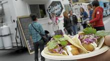 "A customer holds a tempura cod taco in front of the Gastronomo Vagabondo truck at a ""Food Truck Rally"" at Celebration Square in Mississauga, Ontario on Sept. 30, 2011 (Peter Power/The Globe and Mail/Peter Power/The Globe and Mail)"
