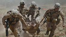 U.S. Marines carry a comrade wounded by an improvised explosive device (IED) to a waiting medevac helicopter, near the town of Marjah in Helmand Province, in this August 21, 2010 file photo. (REUTERS/BOB STRONG/REUTERS/BOB STRONG)