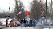 First Nations protesters block the Via Rail train tracks and Wyman's Road near Shannonville, Ont., on March 19, 2014. (Lars Hagberg/The Canadian Press)